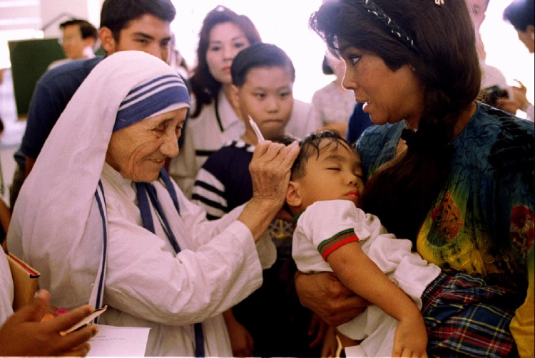 Mother Teresa blesses a sick child held by his mother October 20 at the Missionaries of Charity conv..